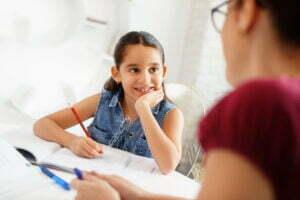 Hispanic Mother Helping Girl Doing School Homework At Home